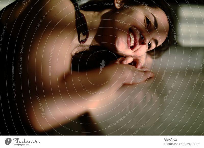 Porträt einer jungen Frau, die mit Kopf und Arm auf dem Tisch liegt, Spiel von Licht und Schatten natürlich hübsch brünett langhaarig lange Haare schlank passen