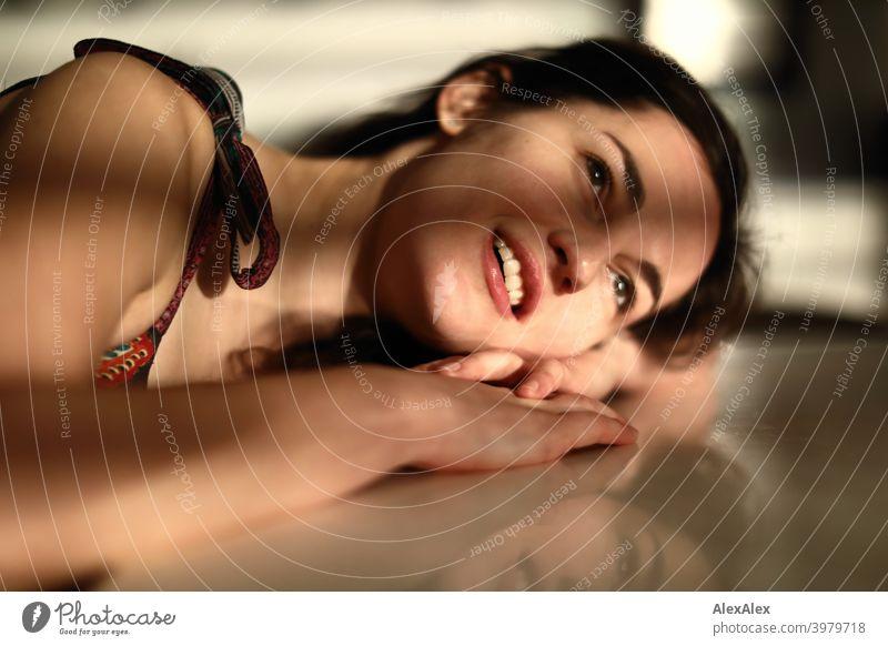 Portrait einer jungen Frau die mit ihrem Kopf und Arm auf dem Tisch liegt, Licht- und Schattenspiel natürlich hübsch brünett langhaarig lange Haare schlank
