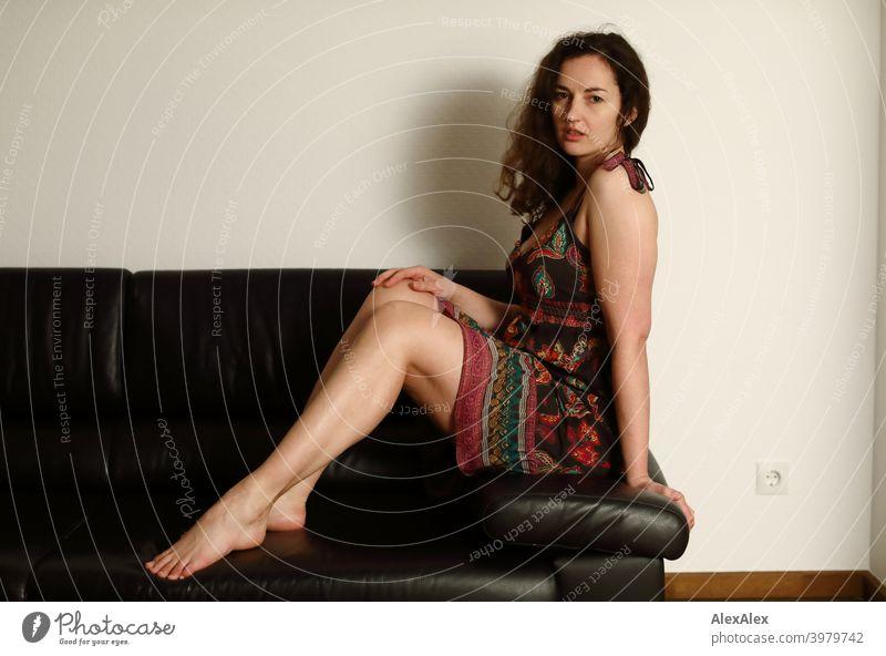 Porträt einer jungen, brünetten, langhaarigen Frau, die barfuß auf einer dunklen Couch im Sommerkleid sitzt natürlich hübsch lange Haare schlank Schulter Haut