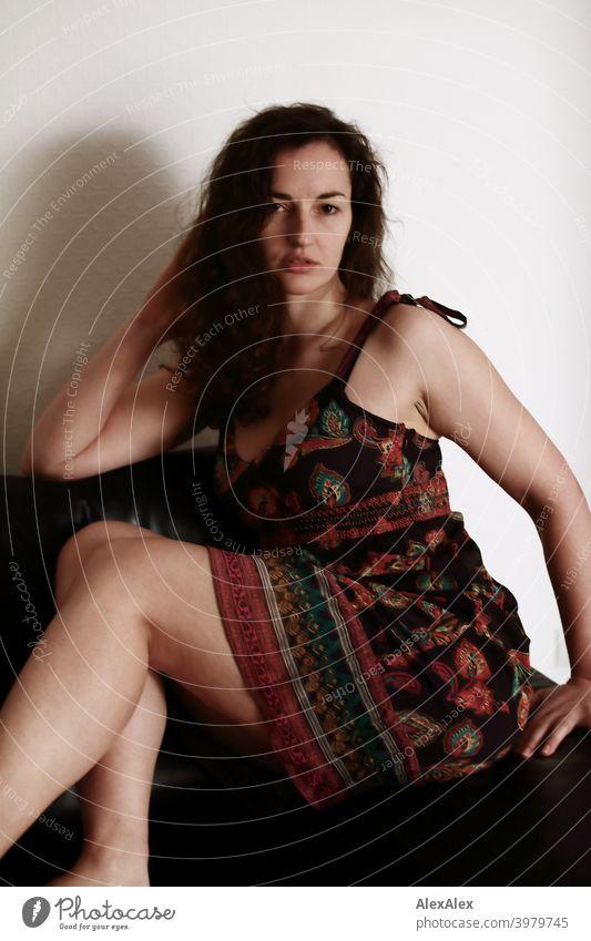Porträt einer jungen, brünetten, langhaarigen Frau, die im Sommerkleid auf einer dunklen Couch sitzt natürlich hübsch lange Haare schlank Schulter Haut seitlich