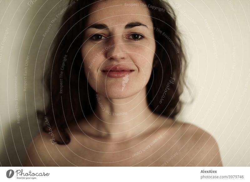 Porträt einer jungen brünetten langhaarigen Frau natürlich hübsch lange Haare schlank passen Klotz Verriegelung Schulter Haut fragen seitlich gerade Gesicht
