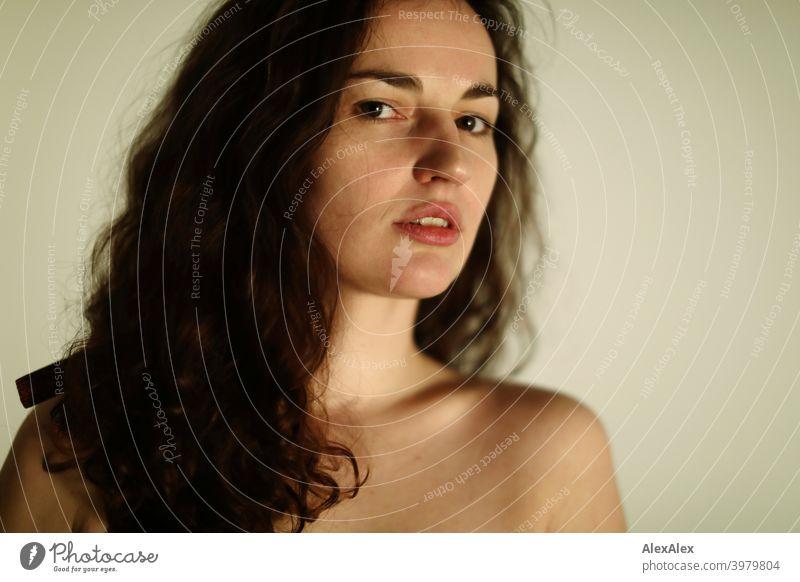 Porträt einer jungen, brünetten, langhaarigen Frau natürlich schoen lange haare schlank passen sperren Verriegelung Schulter haut fragend seitlich direkt