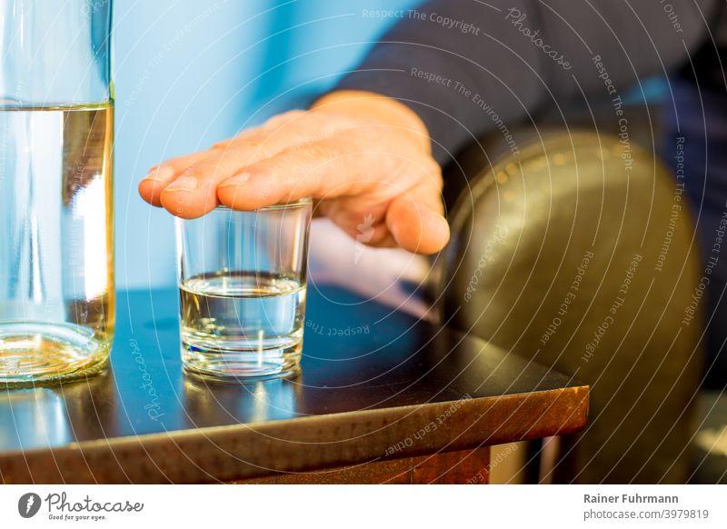 Ein Mann hat seine Hand auf ein Glas gelegt, er möchte nichts trinken. Nahaufnahme Getränk Alkohol Schnaps Bar Tisch Party Nachtleben Club Lifestyle Restaurant