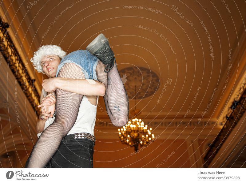 Dieses wilde Paar hat Spaß an der glänzenden Villa. Poshy Kronleuchter im Hintergrund. Ein Junge mit einer Perücke trägt ein Mädchen. Oder entführt sie? Ihre sexy eingefärbten Beine sind wahrscheinlich das Hauptmotiv eines Bildes. Wilde Jugendliche, die die Gesellschaft genießen.