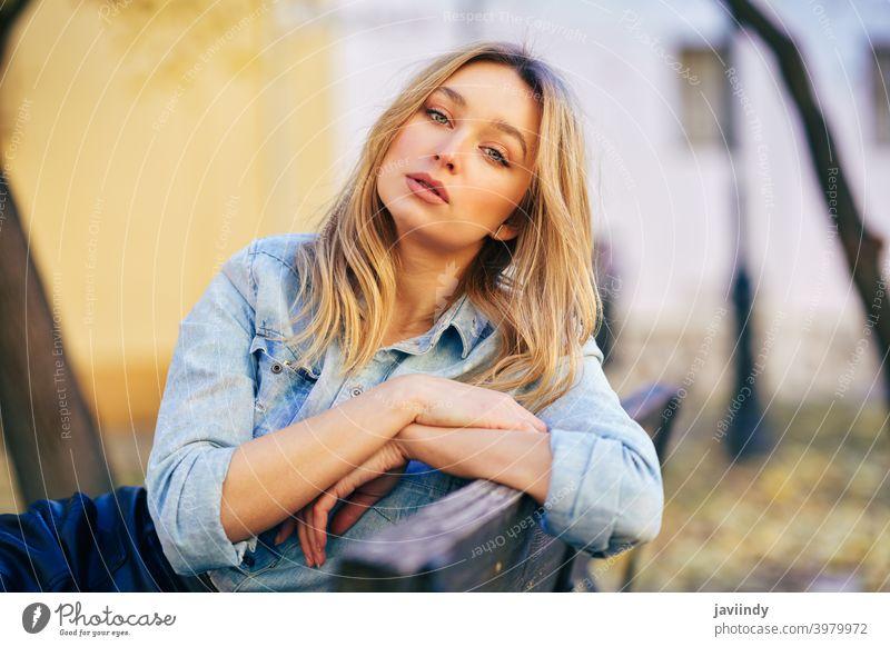 Blonde Frau in Jeanshemd und schwarzem Lederrock sitzt auf einer städtischen Bank. Mädchen blond Russisch blau Auge Porträt Mode im Freien Dame Frisur Person