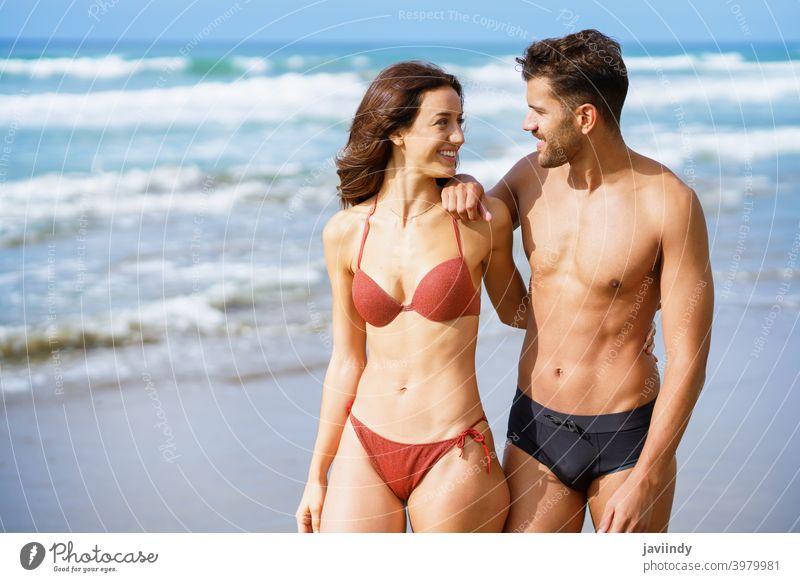 Junges Paar von schönen sportlichen Körper zu Fuß zusammen am Strand Frau Mann Bikini Sommer Freizeit Lifestyle Mädchen Küste im Freien genießend Menschen weiß