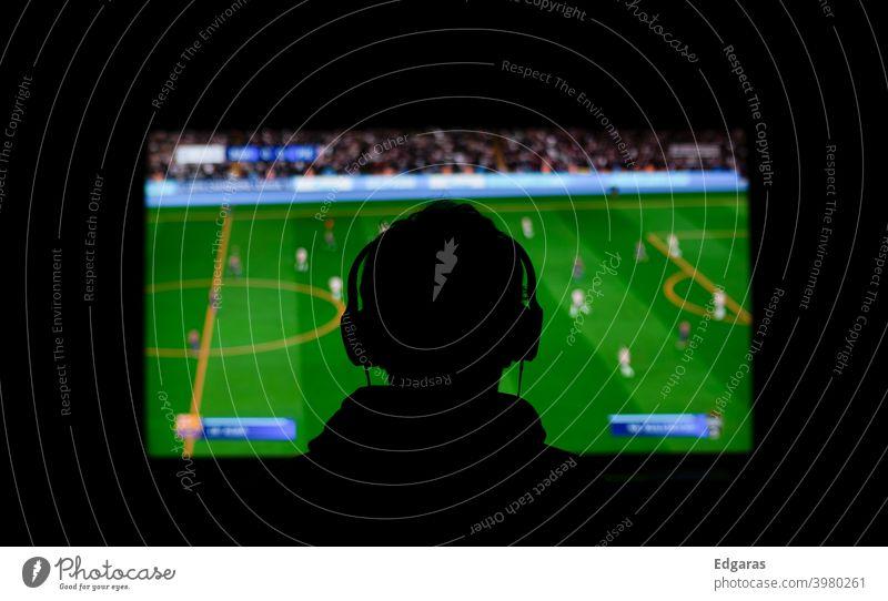 Videospiele spielen oder Fußball schauen Spielen von Videogames Konsole Fußball gucken dunkel FERNSEHER Fernsehen Sport Sportveranstaltung Fußballstadion