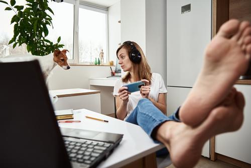 Frau hört Online-Kurs in Kopfhörer, Fernunterricht. Freelancer sitzt am Arbeitsplatz und prokrastiniert. Fauler und abgelenkter Mitarbeiter bei der Fernarbeit