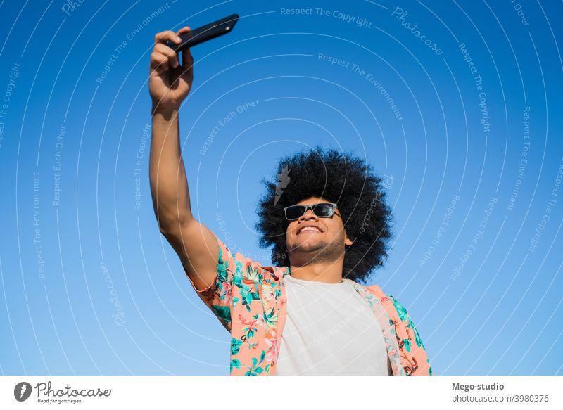 Latino-Mann nimmt ein Selfie mit Telefon im Freien. Latein Mobile urban Tasche Männer reisen Lächeln Konzept Emotion Gerät benutzend Sonnenbrille Sommer