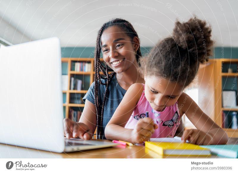 Eine Mutter hilft ihrer Tochter bei der Hausaufgabenbetreuung. Laptop Schule online Schüler Lernen Lifestyle Quarantäne Familie Kinder Menschen absperren