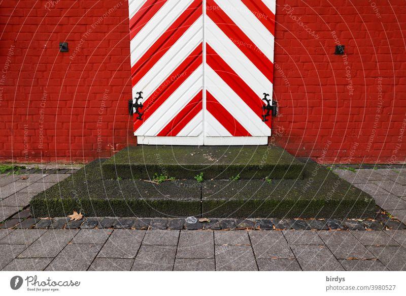Antike Eingangstür in rot-weiß mit Stufen davor. Mittelalterliche Tür, rote Backsteinwand mittelalterlich gestreift diagonal stufen rote Wand Fassade Design