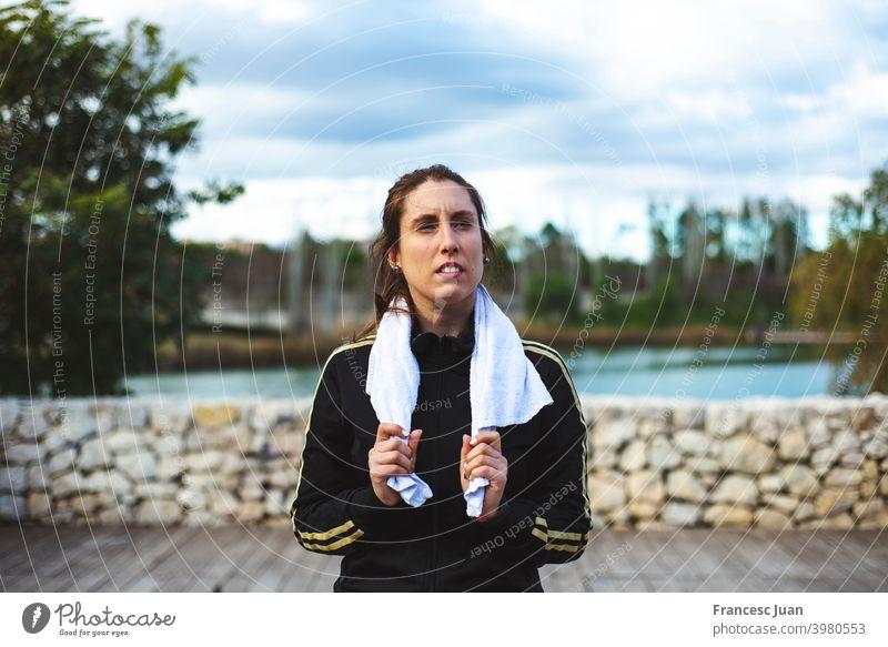 Müde sportliche Frau mit Handtuch entspannt nach hartem Training im Park. passen Mädchen Gesundheit Lifestyle Video Wellness Aerobic allein Gleichgewichtskörper