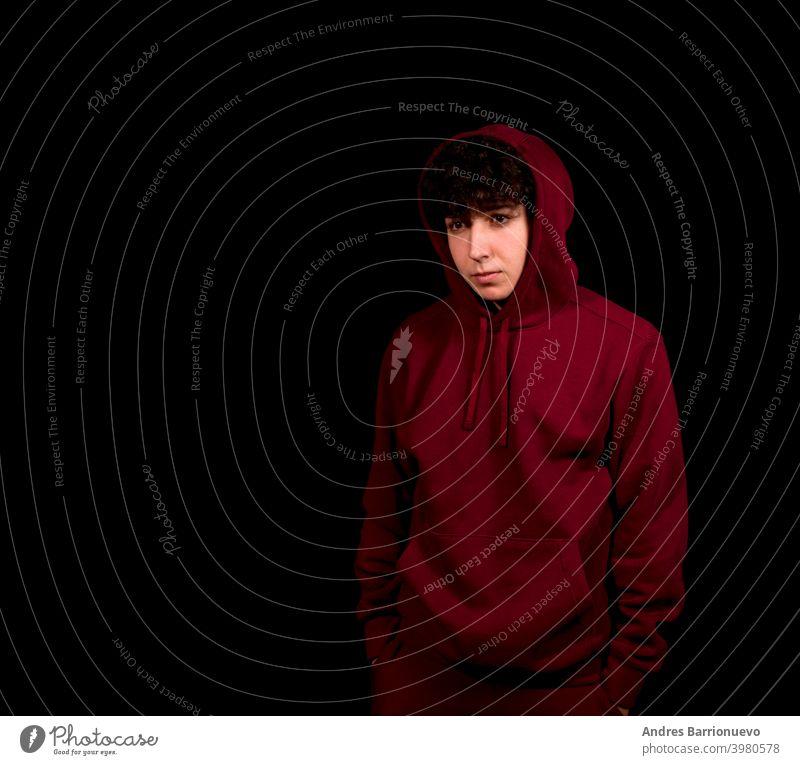 Attraktiver junger Mann mit lockigem Haar posiert auf schwarzem Studio Hintergrund Kaukasier Nahaufnahme nachdenklich Typ Blick Menschen kurz attraktiv