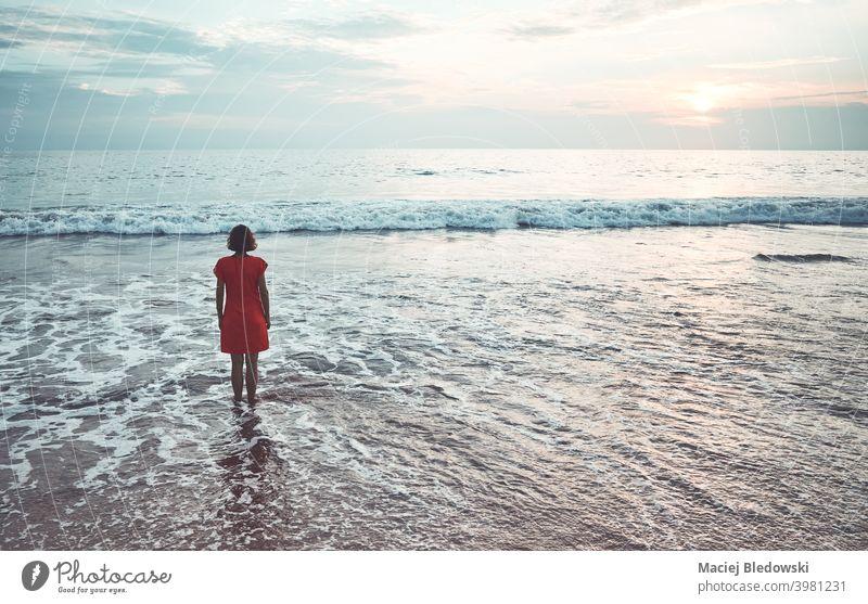 Frau steht bei Sonnenuntergang im Meer. Mädchen Strand Wasser MEER Einsamkeit Depression Sommer Nostalgie verblüht Himmel Horizont winken Sonnenaufgang jung