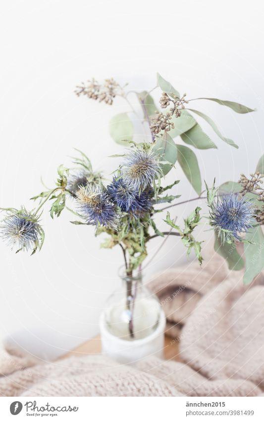 Ein kleiner Strauß Trockenblumen und eine gemütliche Wolldecke Herbst hygge wolle Vase Winter Lifestyle Geborgenheit Hygge bequem Wochenende Erholung Stillleben