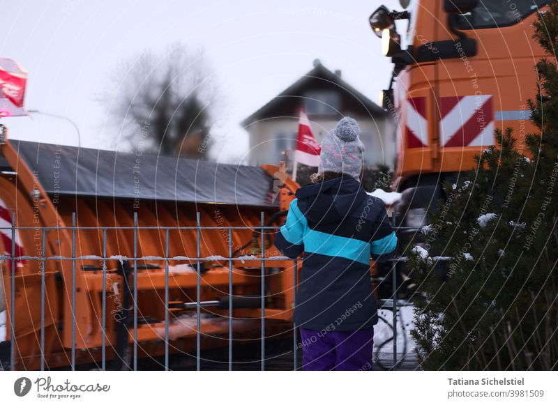 Mädchen blickt auf vorbeifahrendes Winterdienstfahrzeug Schnee kalt Verkehrswege orange Außenaufnahme Wege und Pfade beobachten groß Maschine