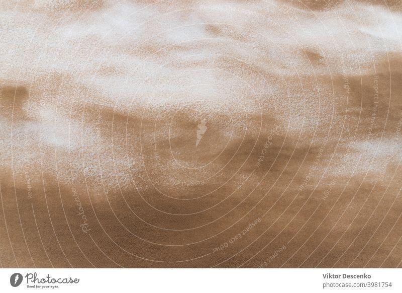 Gelber Sand auf geschmolzenem Schnee in den Dünen Dunes Bildschirmschoner Frost texturiert Wetter Schmutz kalt verschneite Erde nass leer