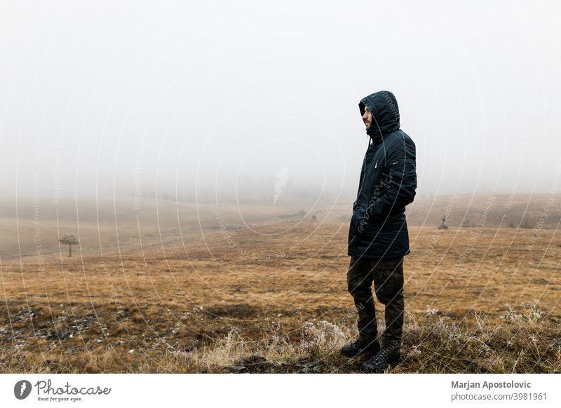 Junger Mann erkundet die Natur an einem nassen Wintermorgen in den Bergen Abenteuer allein Herbst schön Herausforderung kalt Europa Erkundung erkunden Entdecker
