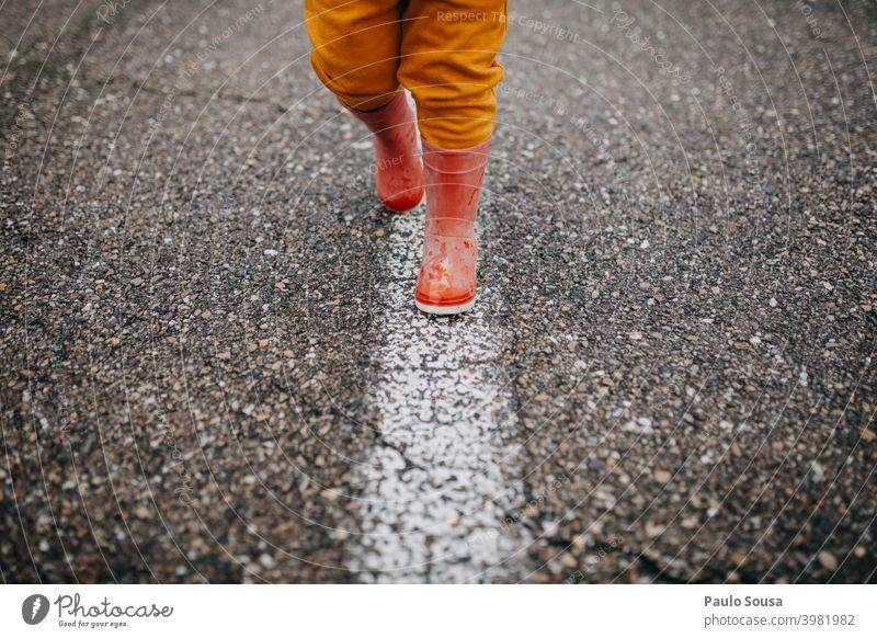 Close up Kind rote Gummistiefel zu Fuß die Linie laufen nass Kindheit Wasser Mensch Freude Außenaufnahme Regen Spielen Farbfoto Herbst Stiefel Tag Wetter Pfütze