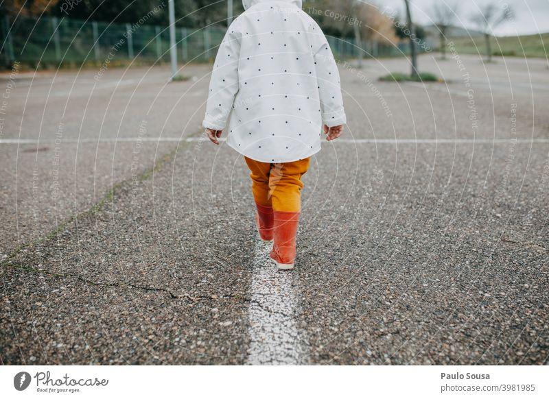 Rückansicht Kind gehend mit roten Gummistiefeln 1-3 Jahre authentisch Spielen Freude Tag Mensch Kindheit Farbfoto Außenaufnahme Freizeit & Hobby mehrfarbig