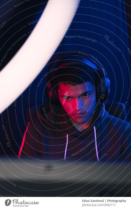 Junger Mann, der ein Live-Videospiel online teilt. Raum Spielen Menschen Cyberspace Entertainment Keyboard Kopfhörer jung Technik & Technologie Spaß Headset