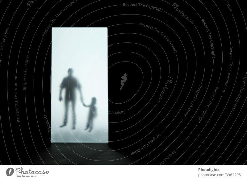 Silhouette eines Kindes und Mannes Umrisse Schatten Mensch dunkel schwarz weiß Innenaufnahme grau Erwachsene Frau Angst gruselig bedrückend Gefühle bedrohlich