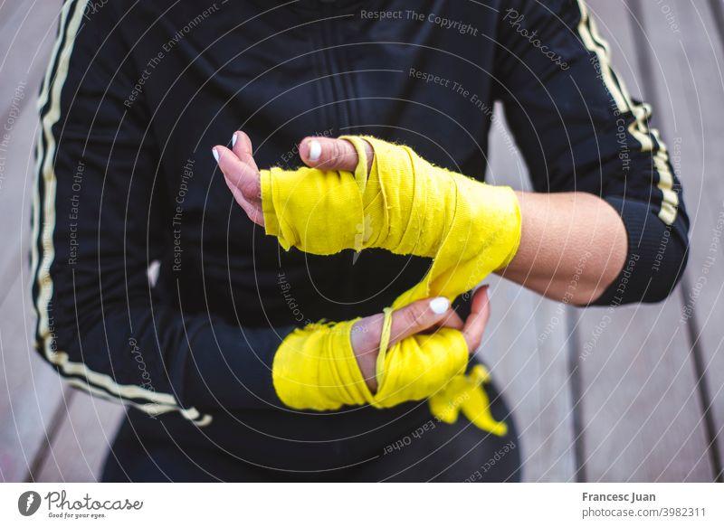 Nahaufnahme einer fitten Frau, die sich Boxbandagen um die Hände legt. aktiv Aktivität Erwachsener Arme Athlet attraktiv bandagieren schwarz Körper Boxer