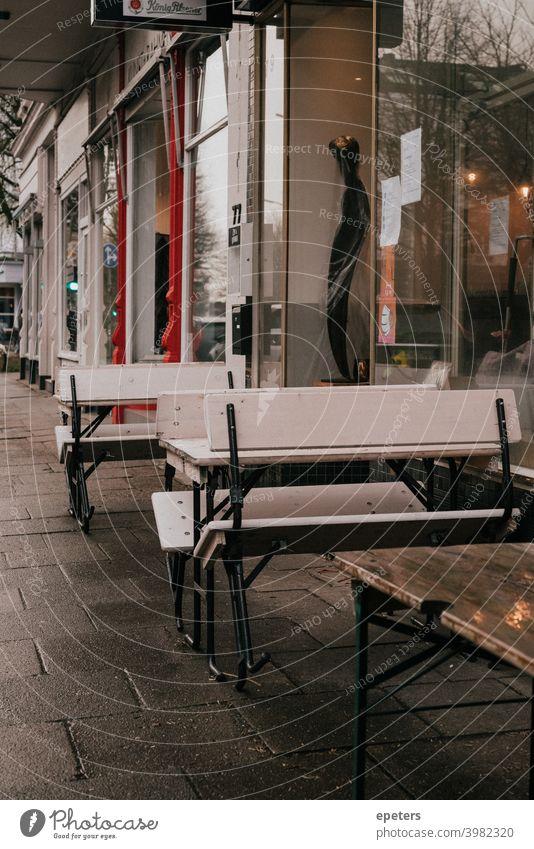 Hochgeklappte Bänke vor einem Café im Corona-Winter hochgeklappt bank bänke tische stühle café cafe trist hamburg corona winter covid covid-19 schließungen