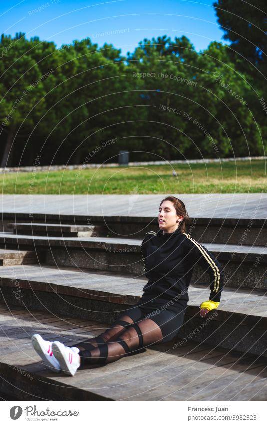 Schöne erwachsene Frau trainiert draußen im Park. Umgekehrte Liegestütze. 30s aktiv Erwachsener Arme Athlet Herbst schön Körper braune Haare Großstadt wolkig