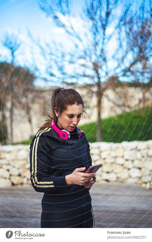 Porträt einer sportlichen jungen Frau mit Kopfhörern, während sie im Freien trainiert. heiter Musik Menschen Sport Erwachsener attraktiv Hintergrund schön blond