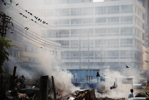 viel Qualm durch Müllverbrennung in der Stadt Umweltverschmutzung Mombasa Kenia Rauch authentisch Stadtzentrum Fassade Stadthaus Stromkabel Vogelschwarm