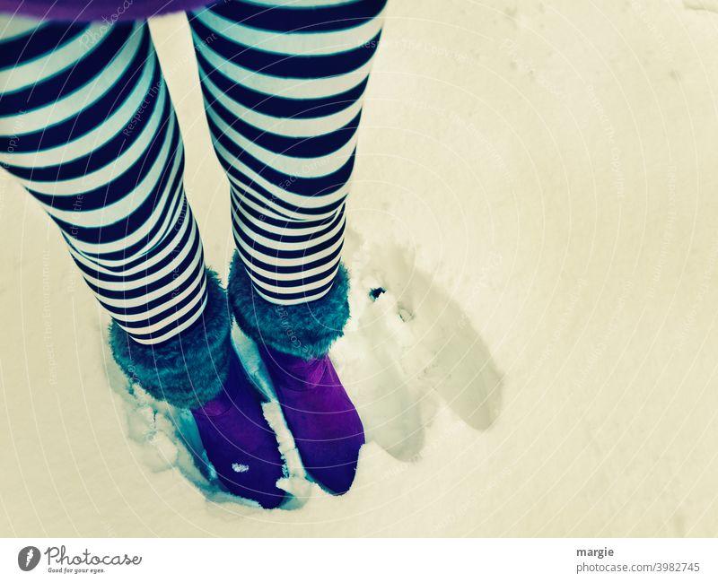 Eine Frau steht im Schnee.  Daneben zwei leere Fußabdrücke. Sie trägt schwarz-weiß geringelte Strümpfe und lila Stiefel. Schuhe Beine Mensch Außenaufnahme