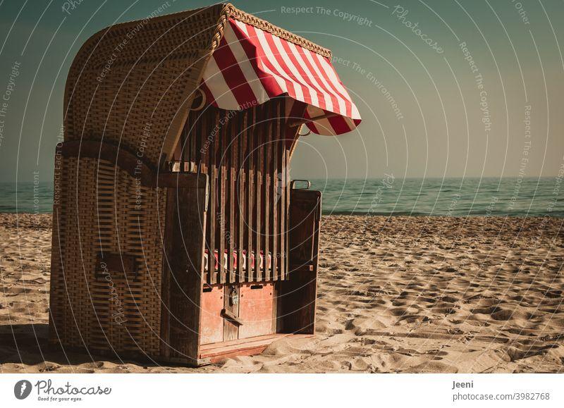 Ganz allein und verschlossen steht er da am Strand im Sand - der Strandkorb mit einem rot-weißen Sonnenschutz Meer Strandsand weiß-rot sonnenschutz Sonnenlicht