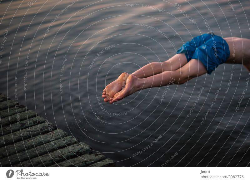 Ein Sprung kopfüber in den See | Der Körper verschwindet gleich im Wasser | Es ist Sommer und es scheinen die letzten Sonnenstrahlen der Abendsonne über dem Wasser