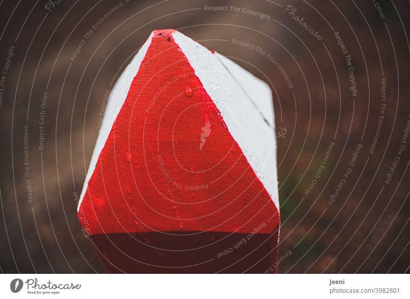 Rettungspunkt im Wald | mit den Farben rot und weiß gekennzeichneter, bemalter, angespitzter Holzpfahl | Notrufpunkt Notfall Rettungskräfte koordinaten Forst