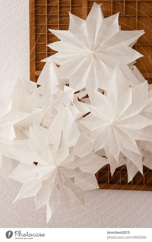 Sterne aus Butterbrotpapier vor einem alten braunen Setzkasten DIY selber machen Butterbrottüten basteln Weihnachten dekorieren schmücken setzkasten