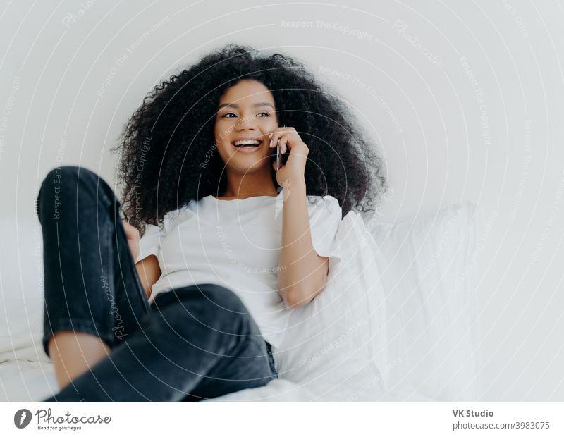 Angenehm aussehende lockige Frau führt ein angenehmes Gespräch, spricht mit einem Freund über Smartphone, während sie sich im Bett entspannt, hat einen freudigen Ausdruck, schaut zur Seite, trägt legere Kleidung. Menschen, Bettzeug, Technik