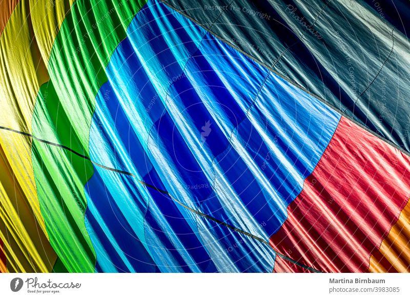 Bunte Außenseite eines entleerenden Heißluftballons Luftballon Regenbogen kreisen Farben Zentrum zentriert Symmetrie Gewebe Spaß farbenfroh Ballonfahren