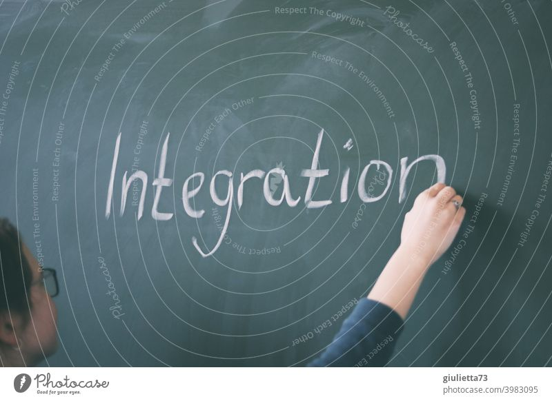 Junge Lehrerin schreibt mit Kreide das Wort Integration an die Tafel Intergration 18-25 Jahre Unterricht Tag Zentralperspektive Frau Schulunterricht Farbfoto