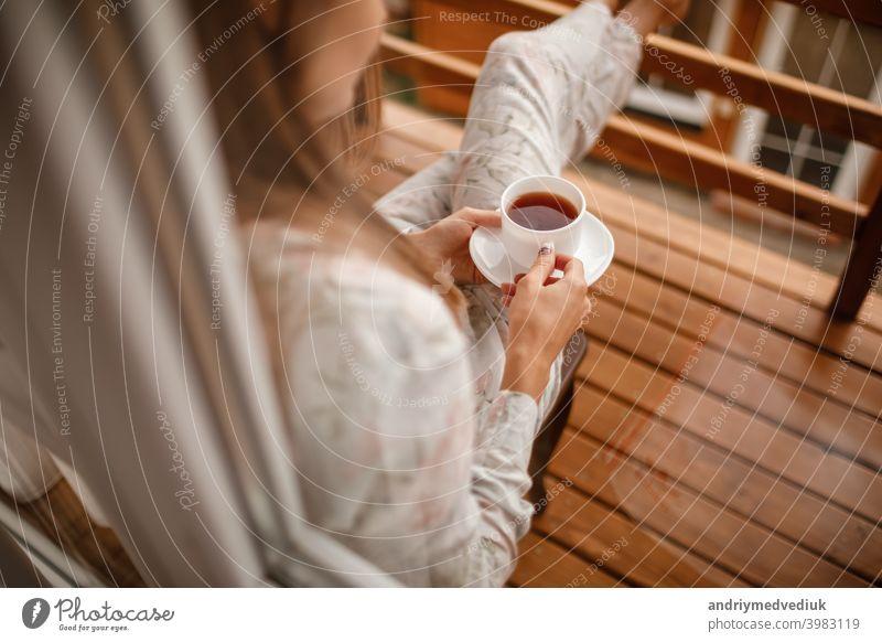 Junge Frau in stilvoller Nachtwäsche trinkt morgens gerne Kaffee oder Tee im Freien auf dem Balkon und schaut auf die Berge. Tasse heimwärts