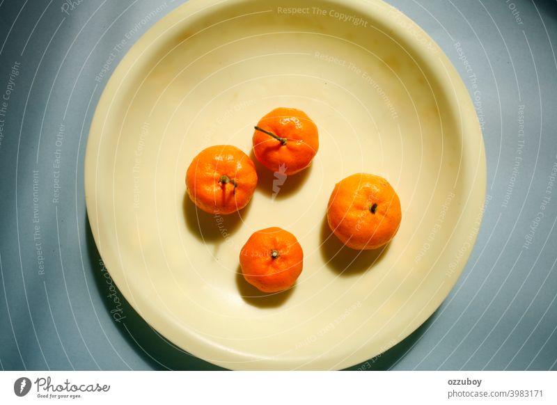 orangefarbene Früchte auf gelbem Teller Vitamin frisch Frucht reif geschmackvoll Zitrusfrüchte Farbe Frische tropisch Hintergrund Diät Lebensmittel natürlich
