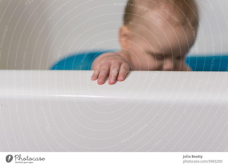 Nahaufnahme von Händen und Fingern des Babys, die den Rand der Badewanne greifen; im Hintergrund sitzt das Baby aufrecht in der blauen Babybadewanne Badezeit