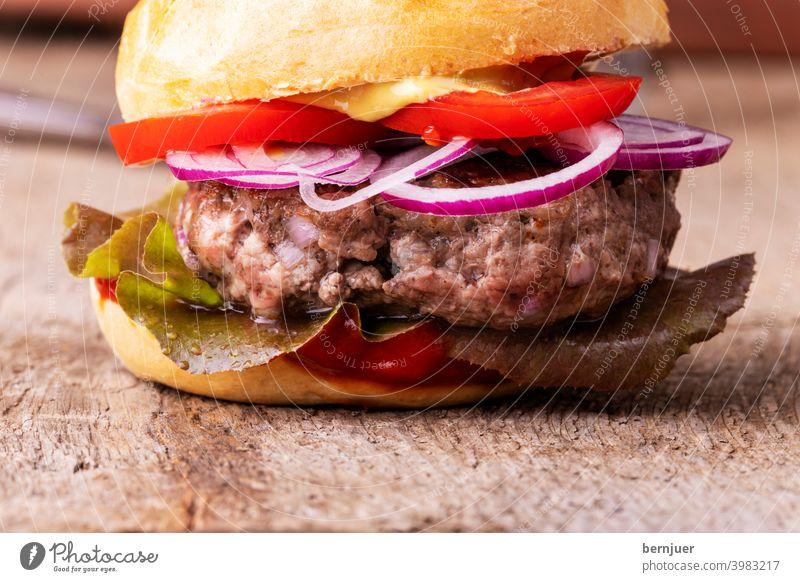 Nahaufnahme eines Hamburgers auf Holz Cheeseburger Hackfleisch Fleisch hausgemacht Zutat bbq schnell Burger Brötchen Zwiebel rot Zwiebelring gegrillt Salat