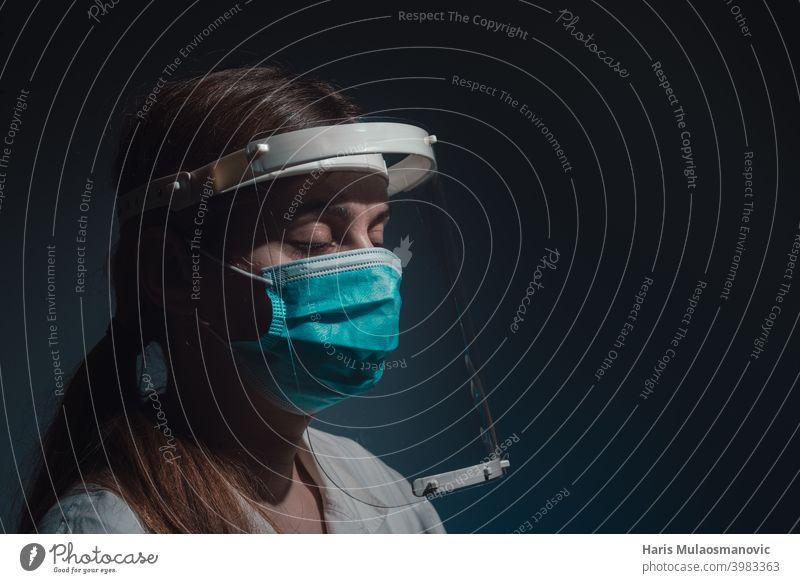Ärztin mit Gesichtsschutz und Maske, geschlossene Augen, Seitenansicht auf dunklem Hintergrund schwarzer Hintergrund Korona-Epidemie Corona-Virus covid-19