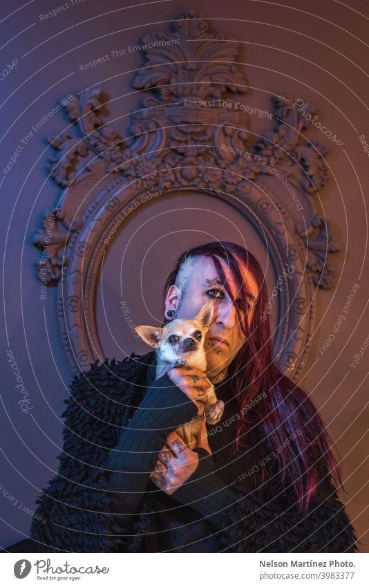 Gerahmtes Porträt eines exzentrischen Rockers mit seinem kleinen Hund. Er hat lange lila Haare. androgyn männlich schön jung Mann feminin Typ Nahaufnahme schwul