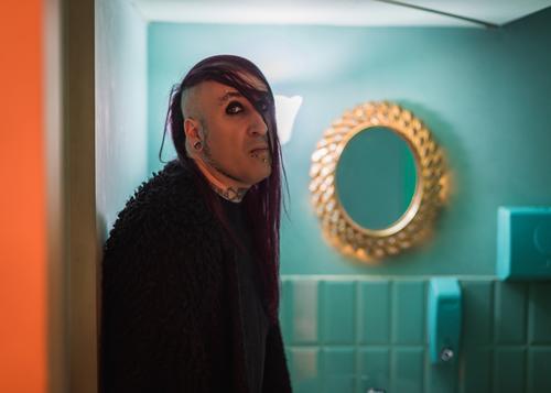 Porträt eines exzentrischen Rocker-Mannes mit langen lila Haaren in einem grünen Badezimmer. androgyn männlich schön jung feminin Typ Nahaufnahme schwul