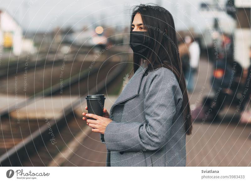 Fröhliches Mädchen in einer Maske steht mit Kaffee in der Hand am Bahnhof und wartet auf den Zug. Verkehr jung Frau schön Eisenbahn Passagier U-Bahn Lächeln