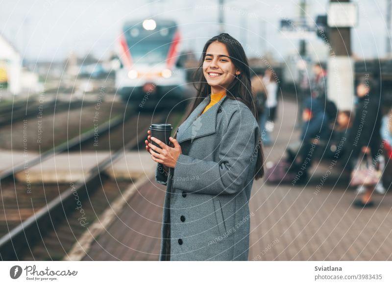 Fröhliches Mädchen steigt am Bahnhof mit Kaffee in der Hand in den Zug ein. Verkehr jung Frau schön Eisenbahn Passagier U-Bahn Lächeln Öffentlich Station Warten