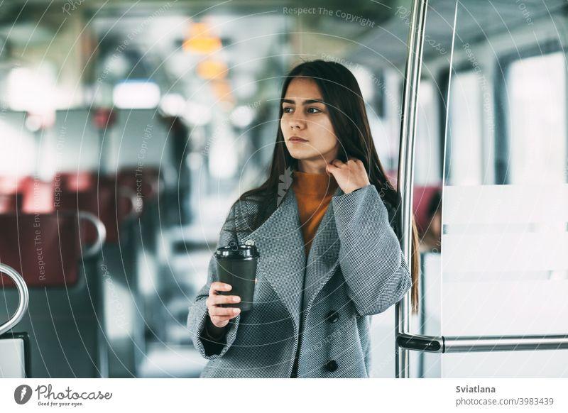 Eine fröhliche Brünette mit Kaffee in der Hand steht im Zug, schaut in die Ferne und lächelt. Verkehr jung Frau schön Eisenbahn Passagier U-Bahn Lächeln