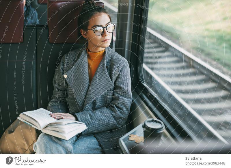 Junges schönes Mädchen in einem Zug, das ein Buch liest, während es in einem Zug reist Passagier Glück Reise Kaffee Tourist Ruhe lesen im Inneren Verkehr jung